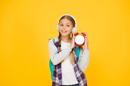 School timing concept. Beginning of lessons. Time go school. School time. Happy girl hold alarm clock counting minutes. Knowledge day. Classes schedule. Schoolgirl hold alarm clock yellow background