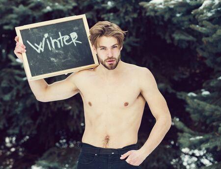 handsome muscular man with winter blackboard outdoor