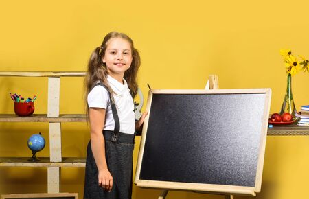 Kid and school supplies on yellow wall background Foto de archivo - 134843200