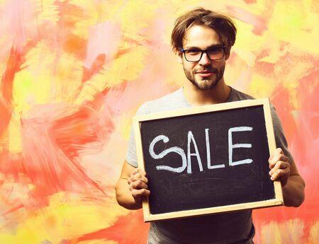 Caucasian bearded sexy macho man holding board with sale inscription