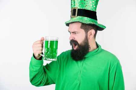 Irish until I pass out. Hipster in leprechaun hat holding beer mug. Irish man with beard drinking green beer. Bearded man toasting to saint patricks day. Celebrating saint patricks day in bar