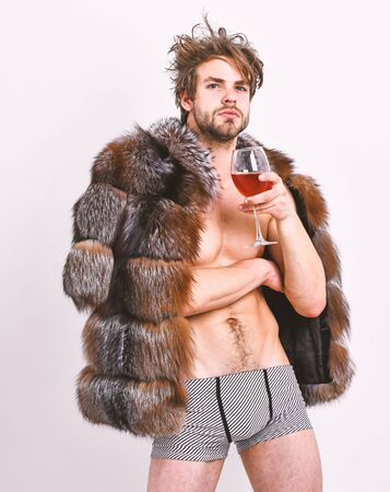 Rich athlete enjoy his life. Sexy sleepy rich macho tousled hair drink wine isolated on white. Fashion and pathos. Richness and luxury concept. Guy attractive rich posing fur coat on naked body