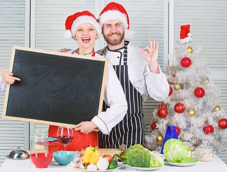 Couple check list ingredients for christmas dinner. Menu for our family. Cooking christmas meal. Man and woman chef santa hat near christmas tree hold blackboard copy space. Christmas recipe concept