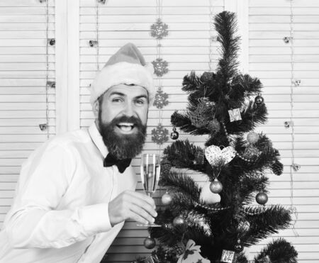 Man with beard and bow tie holds champagne glass. Santa Claus in red hat with happy face sends cheers. Guy near Christmas tree on wooden wall background. Celebration and New Year concept Zdjęcie Seryjne