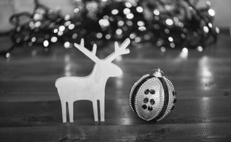 Ball with ornaments and wooden deer toy on blurred colorful garland background. Christmas decor. Symbols of winter holiday christmas. Deer and toy decorative ornament. Merry Christmas concept