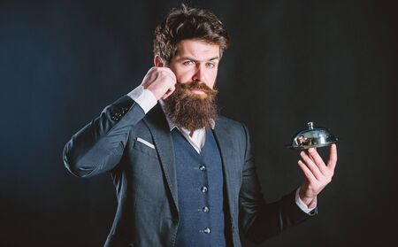 This should be fine. Bearded man chef presenting meal. Waiter man. Perfect recipe. brutal caucasian hold metallic dish. businessman in suit. Mature hipster with beard hold food tray in restaurant Foto de archivo