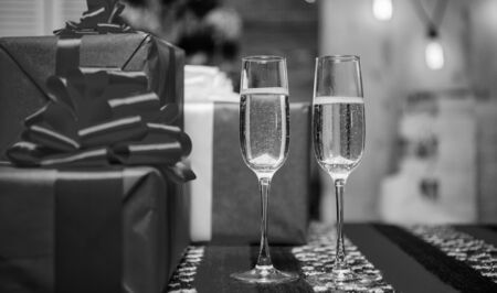 Happy new year and merry christmas. Glass filled sparkling wine or champagne near gift boxes. Cheers concept. New year traditional attribute. Glass of champagne close up. Champagne couple glasses.