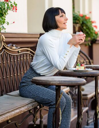 Woman attractive elegant brunette enjoy gourmet coffee cafe terrace background. Pleasant time and relaxation. Delicious and gourmet drink. Girl relax cafe with coffee and dessert. Gourmet concept