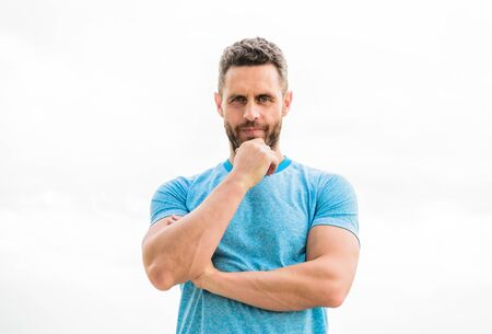 thoughtful man isolated on white. sportsman with athletic body. coach in fitness gym. after workout. man athlete in blue sport tshirt. sportswear fashion. muscular male with beard. serious man