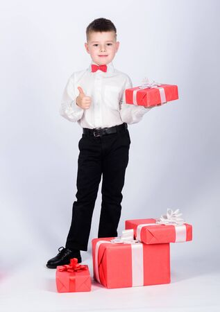happy child with present box. Christmas. Birthday party. Shopping. Boxing day. New year. little boy with valentines day gift. tuxedo style. Happy childhood. Outgoing child choosing product
