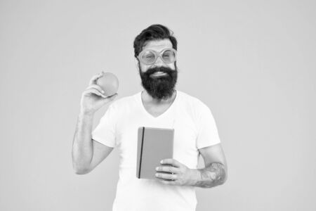 Guy long beard likes orange color. Bright and vibrant. Man bearded cheerful smiling hipster wear orange color sunglasses while hold orange fruit and book notepad. Vitamin source. Total orange Zdjęcie Seryjne