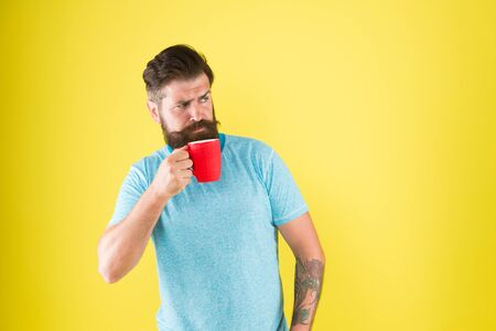 Morning habits lifestyle. Fanatic of coffee culture. Energy concept. Hipster barista yellow background. Coffee shop. Bearded man drink morning coffee. Tea time. Coffee with right proportion of milk Stock fotó