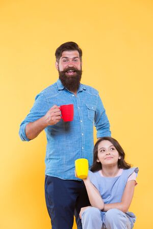 Bearded man and happy little girl holding mugs. Father and daughter drink tea at home. Tea party concept. Good morning. Having coffee together. Water balance and health care. Family drinking tea