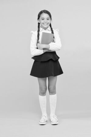 Raising independence. Schoolgirl wear school uniform. Knowledge day. Girl with copy book or workbook. Kid student ready with homework. School girl excellent pupil prepared essay or school project
