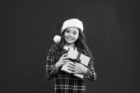 Little girl child in santa red hat. Christmas shopping. New year party. Santa claus kid. Present for Xmas. Childhood. Happy winter holidays. Small girl. gift delivery