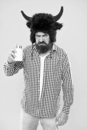 Hate taking pills. Bearded man hold bottle of pills. Hipster with medicine pills or vitamin complex. Sick guy in bull horns hat take cold pills. Health and disease