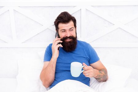 Hello dear. Bearded man using mobile technology in bed. Handsome guy talking on phone and drinking coffee at home. Modern life new technology. Technology concept. Pleasant conversation. Good morning Stock fotó