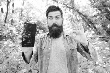 new technology. surprised bearded man hold phone. Mature hipster with beard. got lost in forest. brutal man with phone. hipster style. guy in forest use gps navigation. summer camping. ok gesture