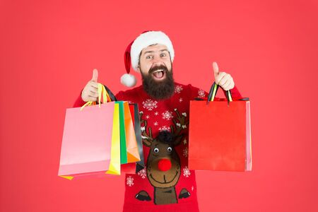 New year clearance sale. Happy hipster give thumbs up with shopping bags. Bearded man enjoy shopping sale. Season sale. Black Friday and cyber monday sale. Christmas eve blowout. Offer and promo