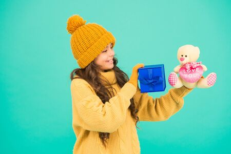 Excitement. st nicolas day. xmas shopping sales. new year souvenir. thank you. keepsake box. small girl warm clothes hold gift. toy bear and present box. surprise for her. favor on winter holidays Foto de archivo - 134880877