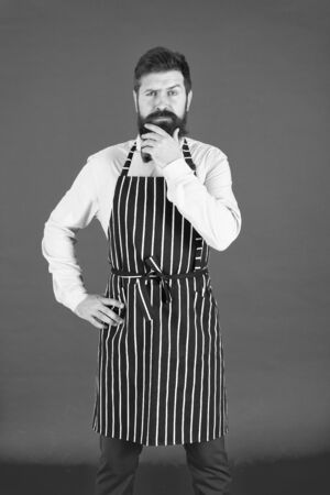 Thinking about new recipe. Elegant waiter man or bartender. Bearded man wearing bib apron. Man cook with beard and mustache in cooking apron. A thoughtful man servant 版權商用圖片