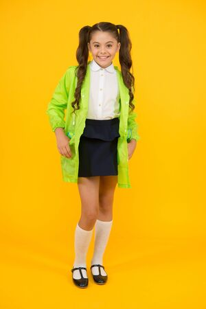 Girl wants it to rain. Happy girl back to school in autumn. Cute little girl smiling on yellow background. Adorable small girl with long brunette hair wearing rain coat for rainy weather Stock fotó