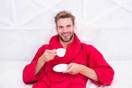 The coffee I choose. Happy man drinking coffee in the morning. Bearded man enjoying his coffee break after bath. Bachelor in bathrobe smiling with cup of coffee in bed