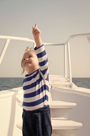 traveling adventures and wanderlust. summer traveling vacation. childhood happiness. happy small boy on yacht. boat traveling by sea. small sailor on boat. funny kid in striped marine shirt Imagens