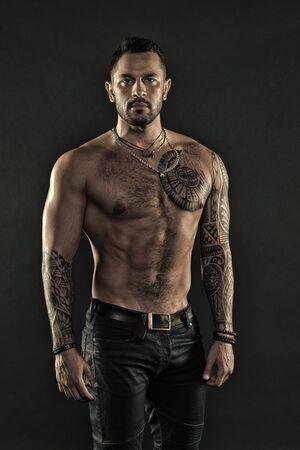 Tattoo-Kunst. Gut aussehender fitter Mann posiert in Jeans mit Tätowierung. Mann gut aussehend mit nacktem Oberkörper muskulös mit Jeans auf dunklem Hintergrund. Muskulöser tätowierter Athlet sieht attraktiv aus. Sport- und Modekonzept Standard-Bild