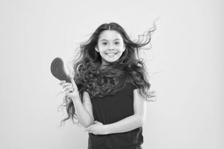 Girl adorable kid long wavy hair yellow background. Wind can also damage hair. Things you doing to damage your hair. Strong persistent winds can create tangles and snags in wavy and curly long hair Stock fotó
