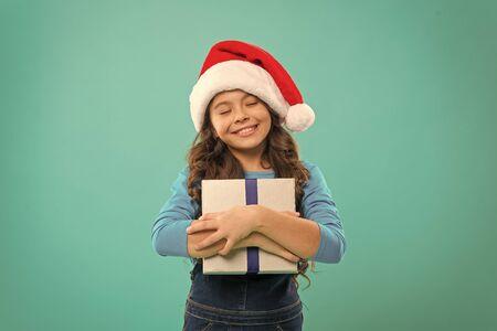 Little girl child in santa hat holding a gift