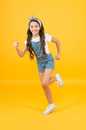 Active lifestyle. Energy inside. Vacation time. Fashion trend. Little fashionista yellow background. Cute kid fashion girl. Summer fashion concept. Girl long curly hair tied headscarf. Hair care 版權商用圖片