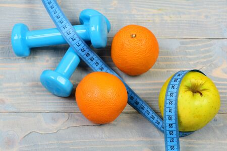 sport and health concept, dumbbells weight with measuring tape ,fruit