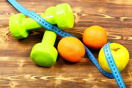 centimeter with dumbbells weight and apple, orange - diet concept