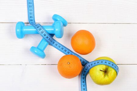 orange, apple with measuring tape, weight dumbbells for diet concept