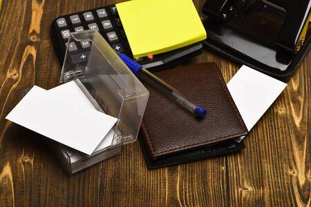 Calculator, puncher, card holder, notes and pen on vintage background