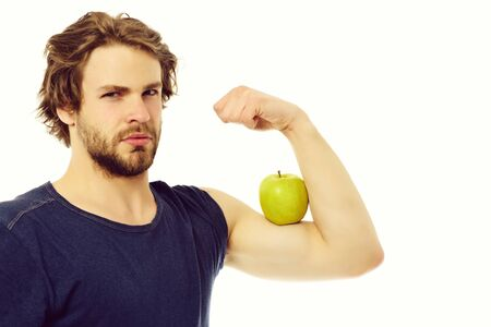 Caucasian guy with confident look holding green apple on muscle Stock fotó