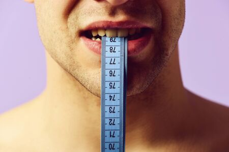 Weight management idea. Male holds blue measuring tape with teeth Stock fotó