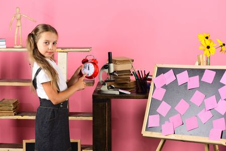 Schoolgirl with proud face holds red alarm clock