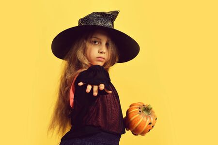 Halloween and costume party concept. Girl with carved orange pumpkin