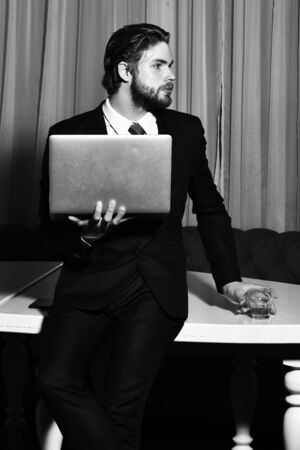 bearded man, businessman with glass of whiskey, cell phone, laptop Stock fotó