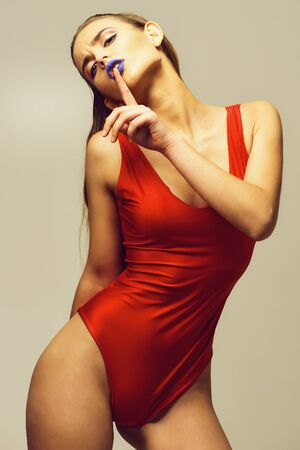 Pretty girl in red bodysuit with blue lips