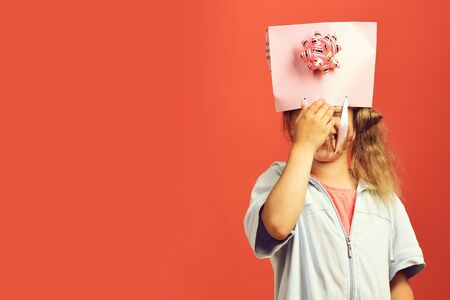 Girl with pink shopping bag and bow. Sale and shopping