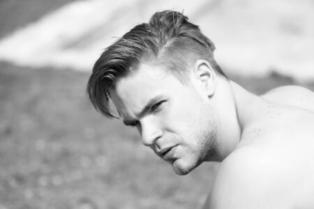 Man with serious face and stylish hairdo looks aside Stock fotó
