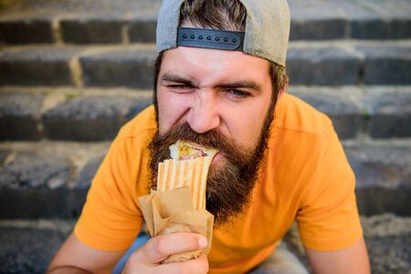 Junk food. Guy eating hot dog. Snack for good mood. Unleashed appetite. Street food concept. Man bearded eat tasty sausage. Urban lifestyle nutrition. Carefree hipster eat junk food while sit stairs