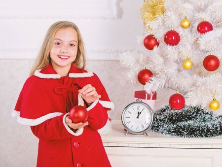 Child red costume hold christmas ornament ball. Christmas ball traditional decor. Kids can brighten up christmas tree by creating their own ornaments. Top christmas decorating ideas for kids room