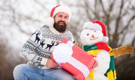 Joyeux et positif. homme barbu construit un bonhomme de neige. Bonne année. L'hiver. Joyeux Noël. l'homme donne un cadeau en plein air. vacances d'hiver. pull chaud par temps froid. hipster heureux prêt pour Noël Banque d'images