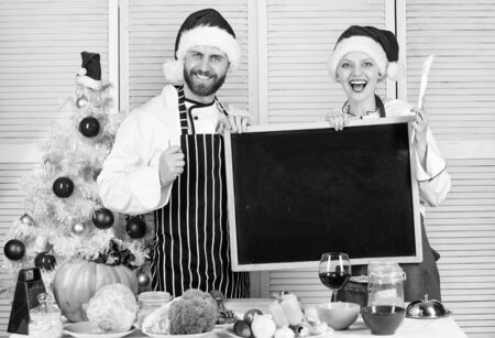 Man and woman chef santa hat near christmas tree hold blackboard copy space. Christmas recipe concept. Cooking christmas meal. Family traditional menu for christmas dinner. Menu for our family Stock Photo