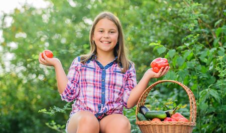 Eat healthy. Summer harvest concept. Organic harvest. Healthy lifestyle. Kid gathering vegetables nature background. Healthy homegrown food concept. Girl cute smiling child living healthy life