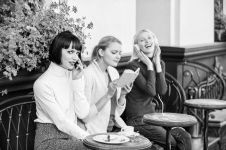 Different interests. Hobby and leisure. Group pretty women cafe terrace entertain themselves with reading speaking and listening. Information source. Female leisure. Weekend relax and leisure Stock fotó